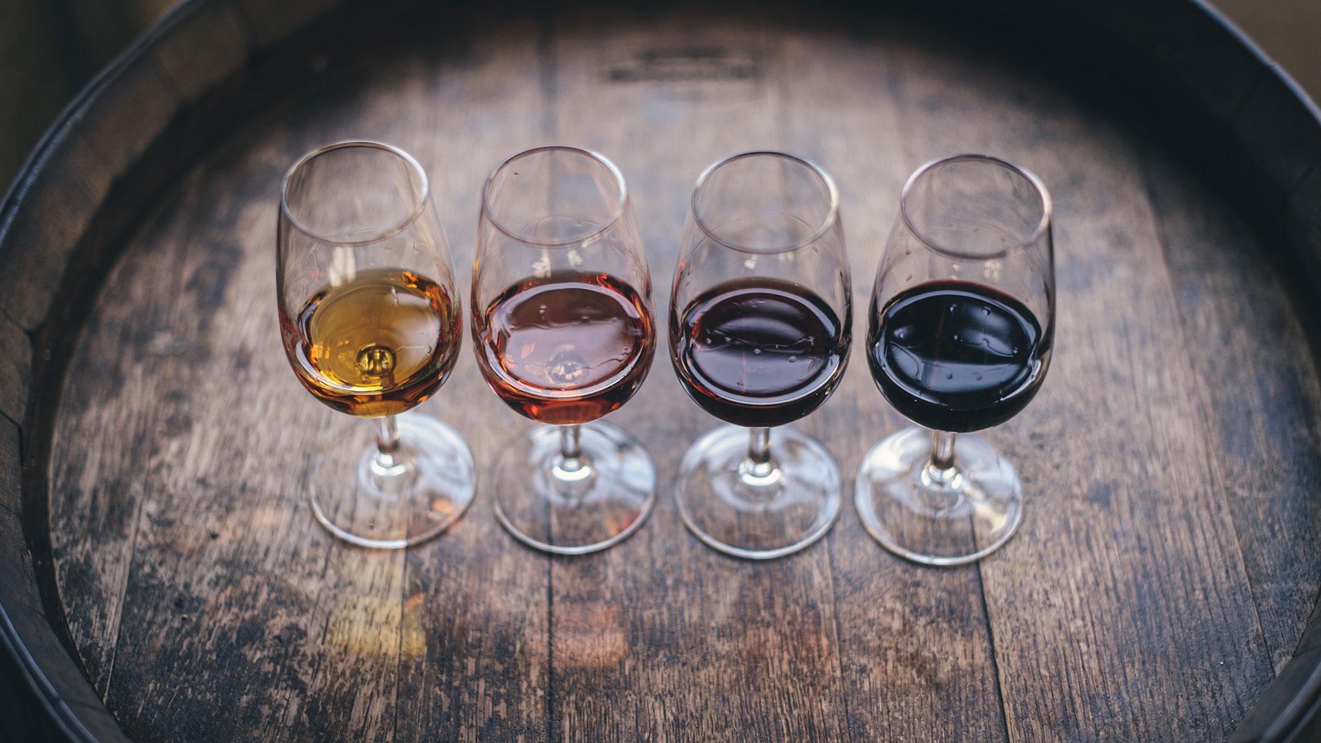 Different wine samples displayed on an oak barrel
